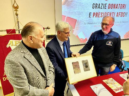 Il vicegovernatore Riccardo Riccardi, che ha accanto il presidente dell'Afds, Roberto Flora, alla consegna della riproduzione della prima tessera del sodalizio, risalente al 1934.