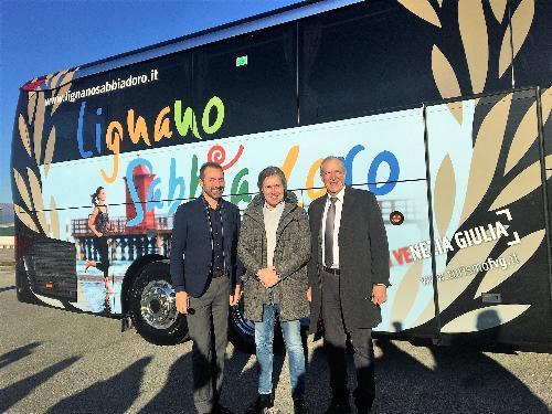 L'assessore regionale al Turismo Sergio Emidio Bini con il direttore di PromoTurismoFvg Lucio Gomiero e l'assessore di Lignano Massimo Brini davanti al nuovo pullman dell'Udinese Calcio con la gigantografia della località balneare