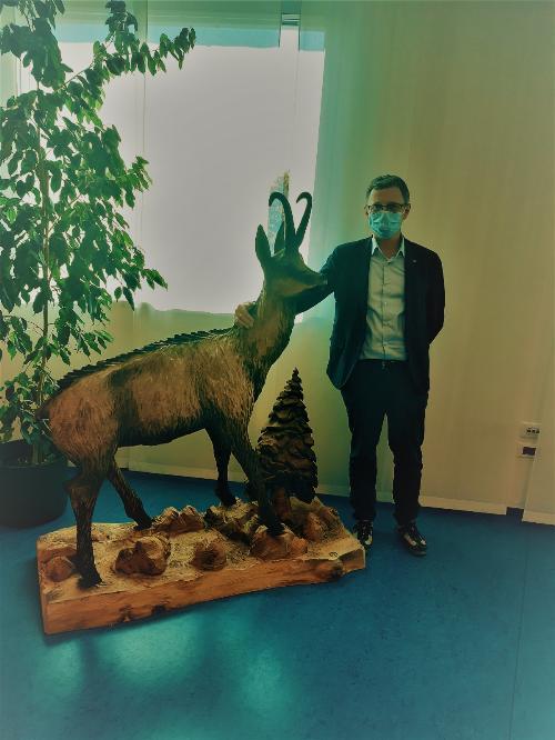L'assessore regionale alle Risorse forestali Stefano Zannier posa con la statua lignea donata dalla Falegnameria regionale di Fusine, opera di Roberto Filaferro