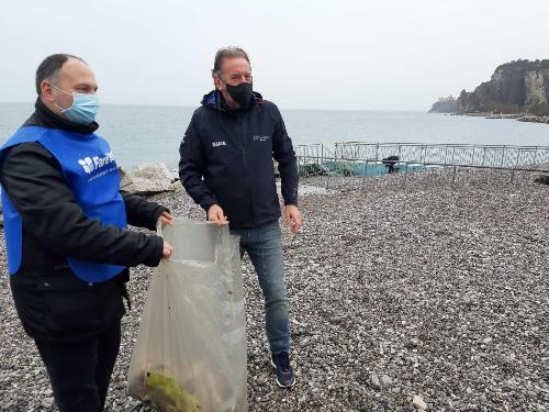 L'assessore alla Difesa dell'ambiente, Fabio Scoccimarro, impegnato assieme a un volontario nella raccolta della plastica a Sistiana